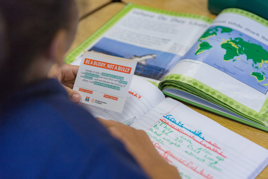 An over the shoulder photo of an elementary student in class with a textbook, notebook, and an anti-bullying info card.