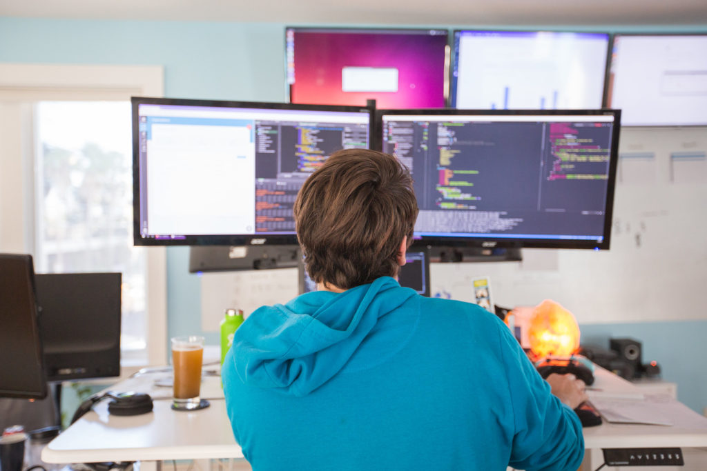 A casually dressed worker at a desk analyzing code on two monitors.